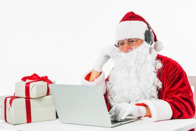 Święty mikołaj przy stołowym używa laptopem