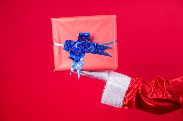 Święty mikołaj ręka trzyma pudełko na prezent boże narodzenie na czerwonym tle.
