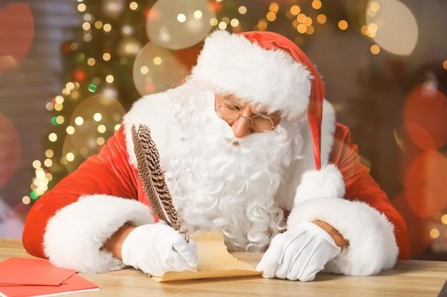 Święty mikołaj robi listę prezentów przy stole