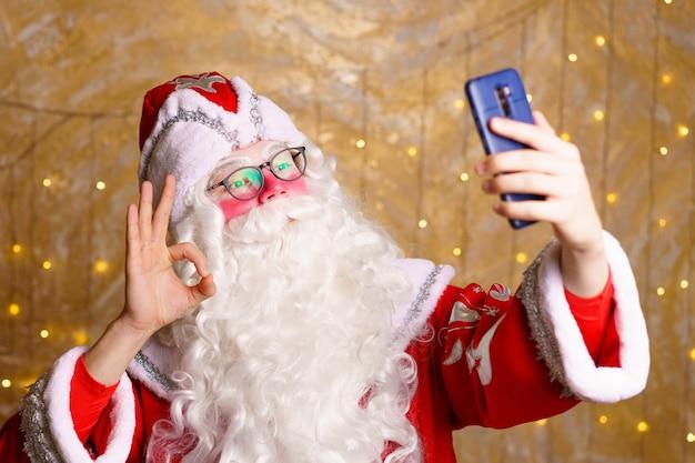 Święty mikołaj robi zdjęcia selfie noc bożonarodzeniowa dostawa prezentów zaczarowane marzenia z dzieciństwa rozmowa wideo