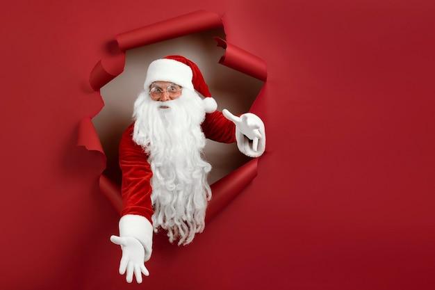 Święty mikołaj rozłożył ramiona w różnych kierunkach i patrzy emocjonalnie przez papierową dziurkę. brodaty mężczyzna w santa hat patrząc przez dziurę na czerwonym papierze.