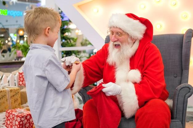 Święty mikołaj rozmawia i bawi się w niespodzianki z dziećmi w centrum handlowym. świąteczne wyprzedaże i