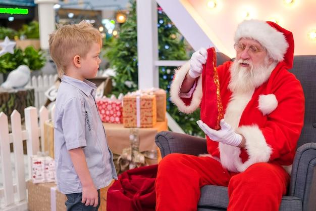 Święty mikołaj rozmawia i bawi się w niespodzianki z dziećmi w centrum handlowym