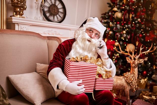 Święty mikołaj siedzi na kanapie i rozmawia przez telefon komórkowy przy kominku i choinki z prezentami. nowy rok i wesołych świąt, koncepcja wesołych świąt