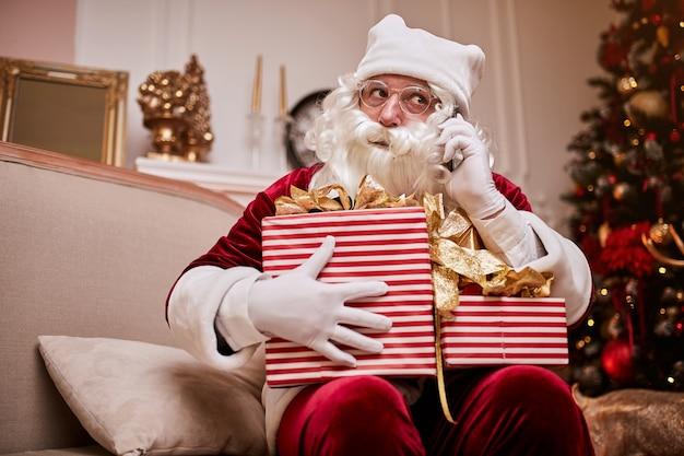 Święty mikołaj siedzi na kanapie i rozmawia przez telefon komórkowy przy kominku i choinki z prezentami.