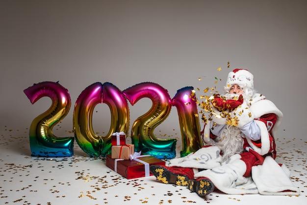 Święty mikołaj siedzi na podłodze z prezentami i balonami powietrznymi 2021.