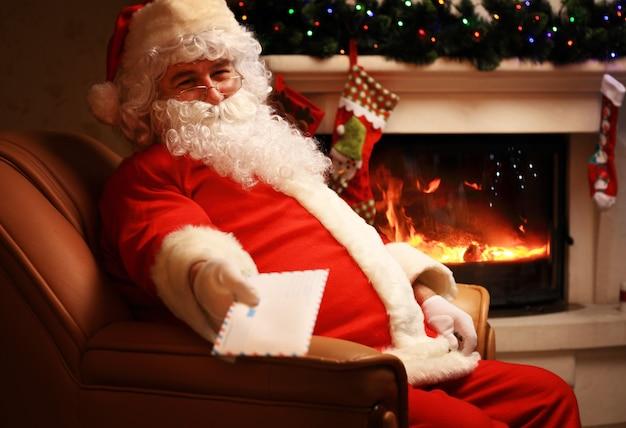 Święty mikołaj siedzi przy choince, trzyma świąteczne listy i odpoczywa przy kominku. dekoracja domowa