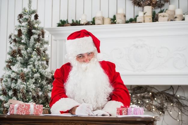Święty mikołaj siedzi przy stole i pisze na papierze