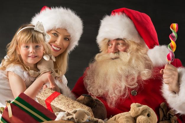 Święty mikołaj siedzi w domu z rodziną - mała dziewczynka i jej matka i dawać prezentom