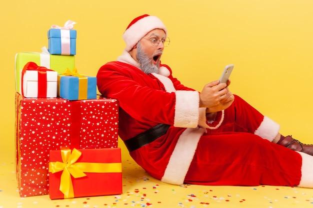 Święty mikołaj siedzi w pobliżu prezentów noworocznych i za pomocą smartfona, czytając szokującą wiadomość.