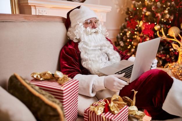Święty mikołaj siedzi w swoim domu i czyta e-maile na laptopie z ñ życzeniami bożonarodzeniowymi lub listą życzeń przy kominku i drzewku z prezentami. nowy rok i wesołych świąt, koncepcja wesołych świąt