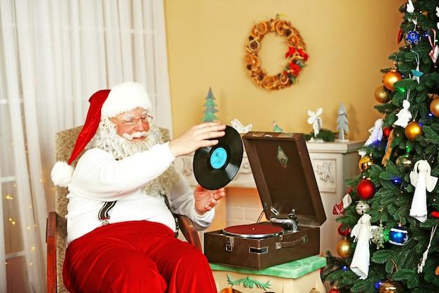 Święty mikołaj siedzi w wygodnym fotelu w pobliżu retro gramofonu w domu