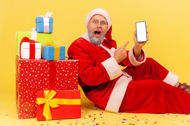 Święty mikołaj siedzi wskazując biały pusty ekran inteligentnego telefonu, otoczony prezentami świątecznymi.