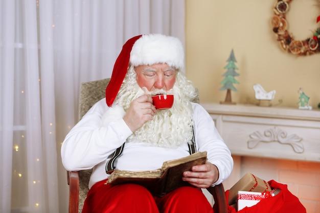 Święty mikołaj siedzi z książką w wygodnym fotelu przy kominku w domu