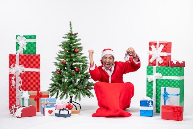 Święty mikołaj siedzi z pudełka na prezenty i drzewo