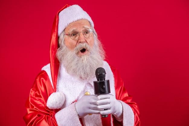 Święty mikołaj śpiewa lub mówi do mikrofonu studyjnego. wesołych świąt. nadawca. spiker. awans. koncepcja muzyki świątecznej