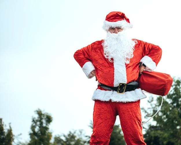 Święty mikołaj stoi z rękami opartymi na biodrach i łapie swoją czerwoną torbę. czas świąt