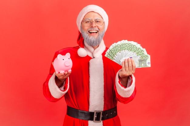Święty mikołaj stojący trzymając banknoty euro i skarbonka, patrząc na kamery z uśmiechem.