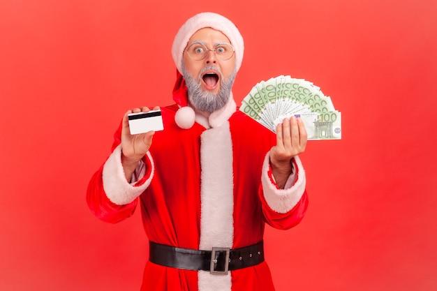 Święty mikołaj stojący z banknotami euro i kartą kredytową w rękach, zszokowany cashbackiem.