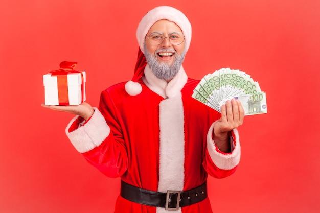 Święty mikołaj stojący z pudełkiem prezentów świątecznych i dużą ilością pieniędzy w rękach.