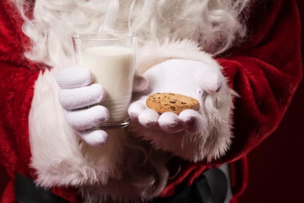 Święty mikołaj trzyma ciastko i szklankę mleka