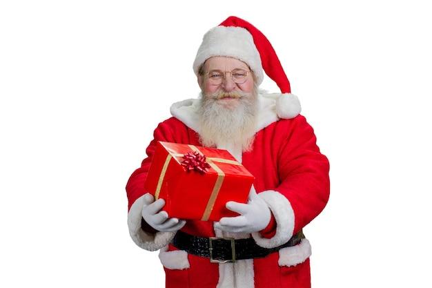 Święty mikołaj trzyma czerwone pudełko z teraźniejszością.