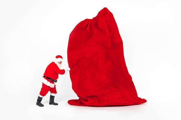 Święty mikołaj trzyma gigantyczną boże narodzenie torbę