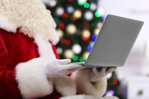 Święty mikołaj trzyma laptopa na choince