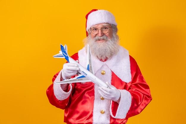 Święty mikołaj trzyma mały samolocik na żółtym tle. koncepcja podróży świątecznych