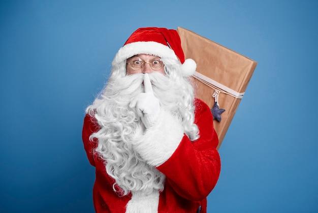 Święty mikołaj trzyma prezenty świąteczne za jego plecami