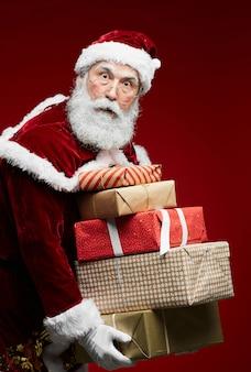 Święty mikołaj trzyma prezenty świąteczne