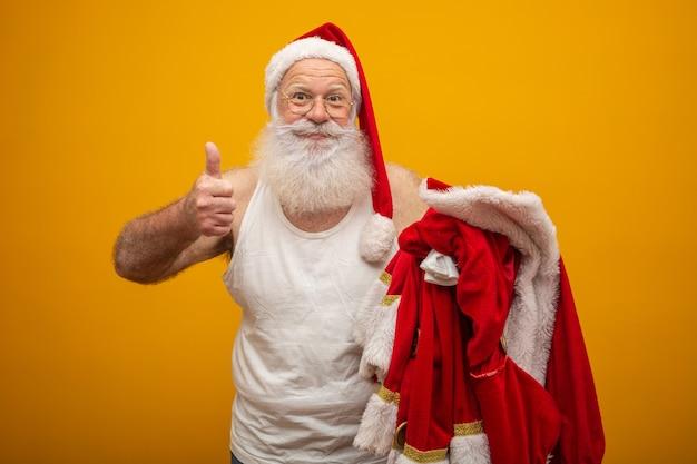 Święty mikołaj trzyma swoje ubrania przed lub przed dostarczeniem prezentów.