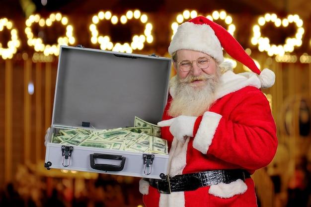 Święty mikołaj trzyma walizkę z pieniędzmi.