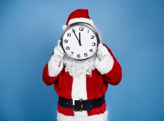 Święty mikołaj trzyma zegar przed jego twarzą
