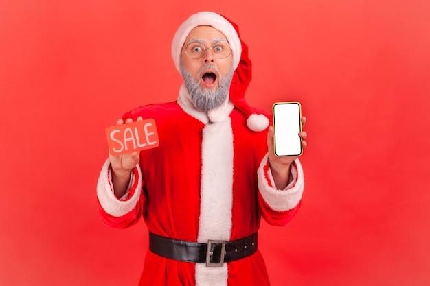 Święty mikołaj trzymając inteligentny telefon z pustym ekranem i kartą sprzedaży, ogromne rabaty.