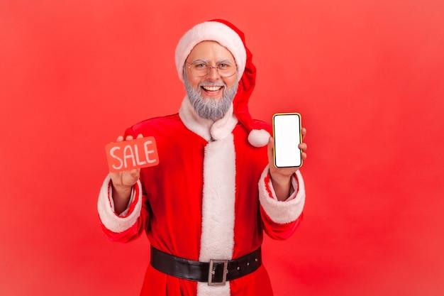 Święty mikołaj trzymając smartfon z pustym wyświetlaczem i kartą sprzedaży w ręce, aplikacja rabatowa.