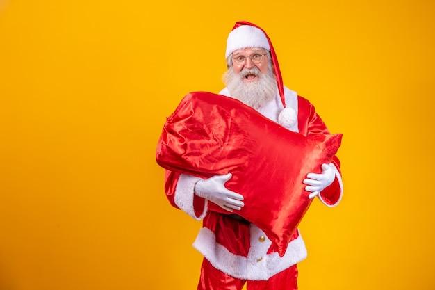 Święty mikołaj trzymający torbę pełną prezentów