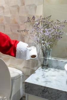 Święty mikołaj używa papieru toaletowego w toalecie domu