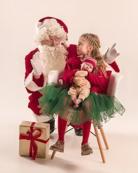Święty mikołaj w czerwonym stroju z małą dziewczynką i dzieckiem na białym tle