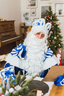 Święty mikołaj w niebieskim futrze czyta list od dziecka na tle choinki.