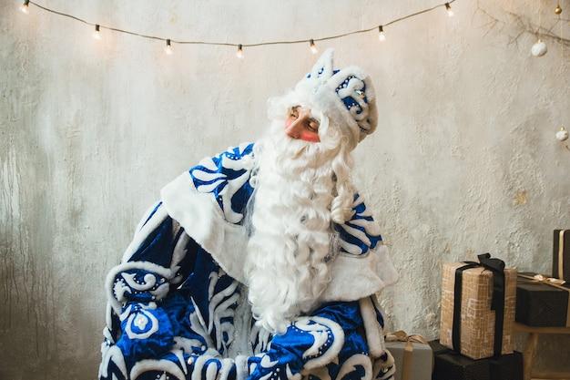Święty mikołaj w niebieskim futrze siedzi w ciepłym pokoju i patrzy w kamerę.