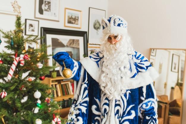 Święty mikołaj w niebieskim futrze w świątecznym wnętrzu zdobi choinkę.