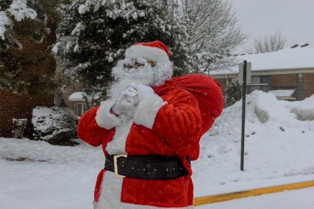 Święty mikołaj wchodzi do domu w wigilię z torbą prezentów