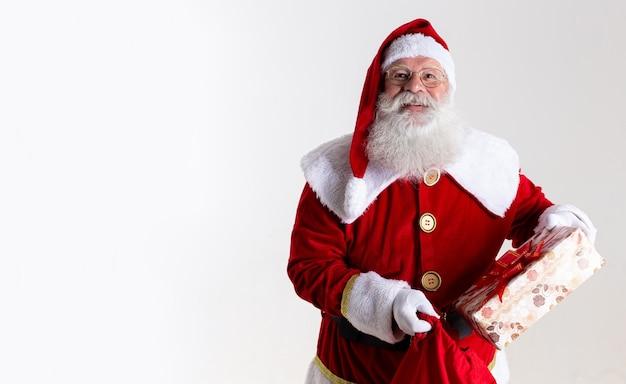 Święty mikołaj wręcza prezenty do aparatu. otrzymywanie prezentów świątecznych. imprezy noworoczne.