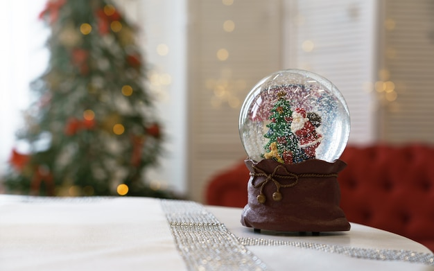 Święty mikołaj wśrodku śnieżnej piłki z dekorującą choinką w tle