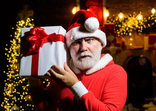 Święty mikołaj z brodatym mężczyzną w stroju świętego mikołaja poważny święty mikołaj trzyma pudełko na boże narodzenie