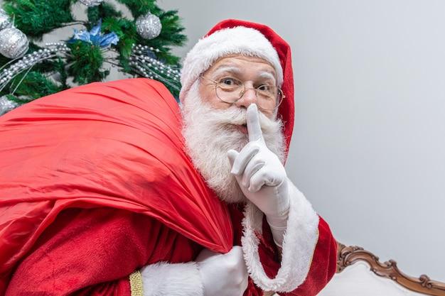 Święty mikołaj z czerwonym workiem, trzymając palec wskazujący ustami i patrząc na kamery