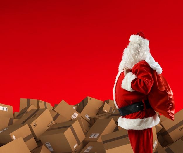 Święty mikołaj z dużą ilością kartonów do dostarczenia