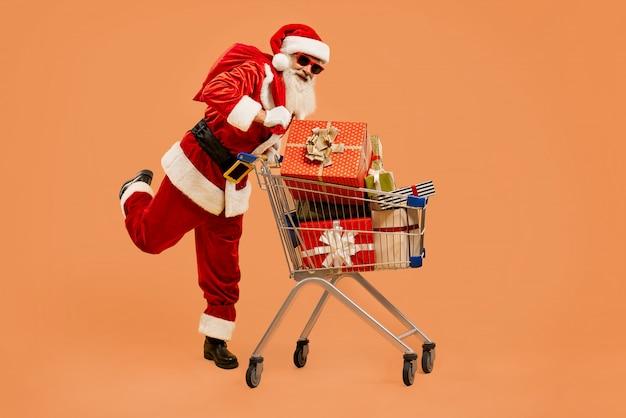 Święty mikołaj z koszykiem pełnym pudełek prezentowych