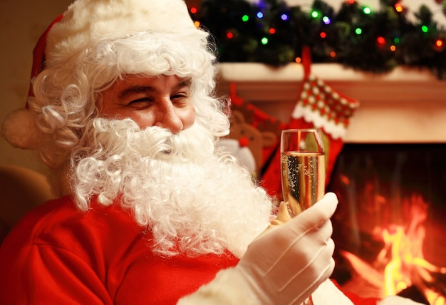 Święty mikołaj z lampką szampana wina musującego w pobliżu choinki